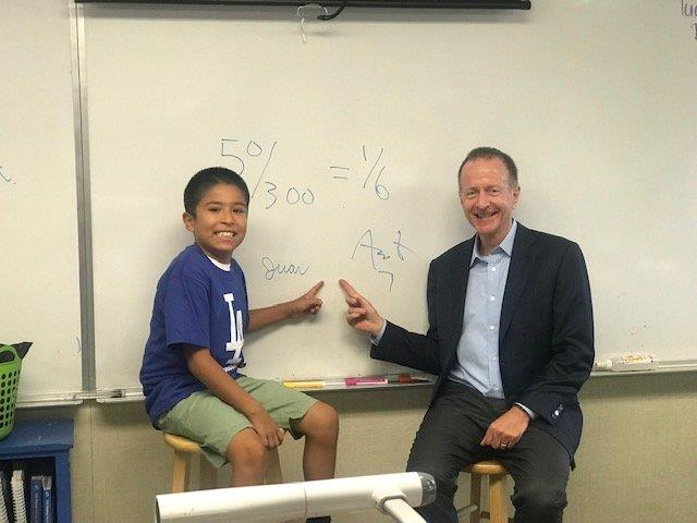 Los Angeles Schools superintendent Austin Beutner congratulates a student on his math work on the first day of school